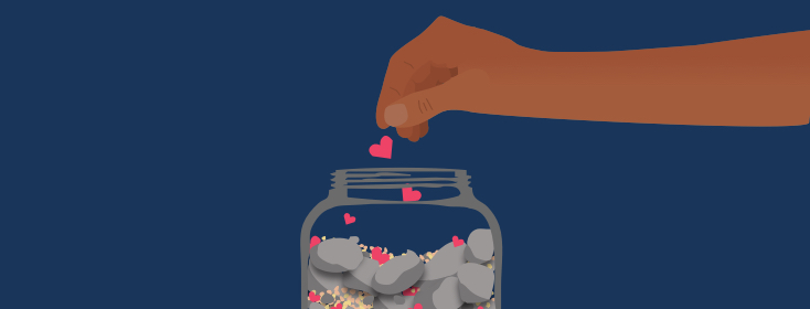 a hand dropping a heart into a jar filled with rocks and sand.