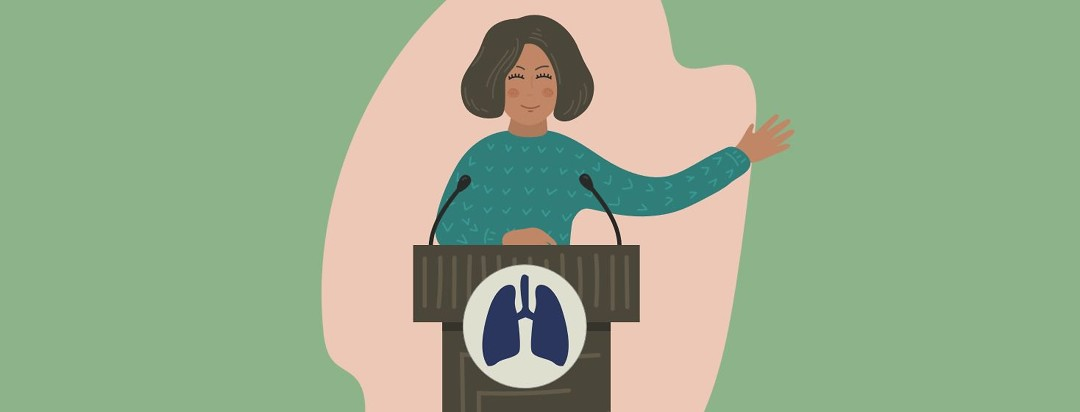 Woman speaking behind a podium with an image of lungs on the front