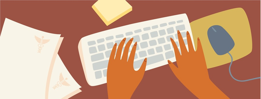 Hands are working at a desk while medical papers sit next to the keyboard