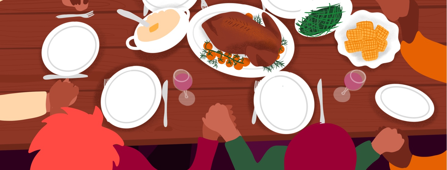A family holds hands around a holiday dinner table