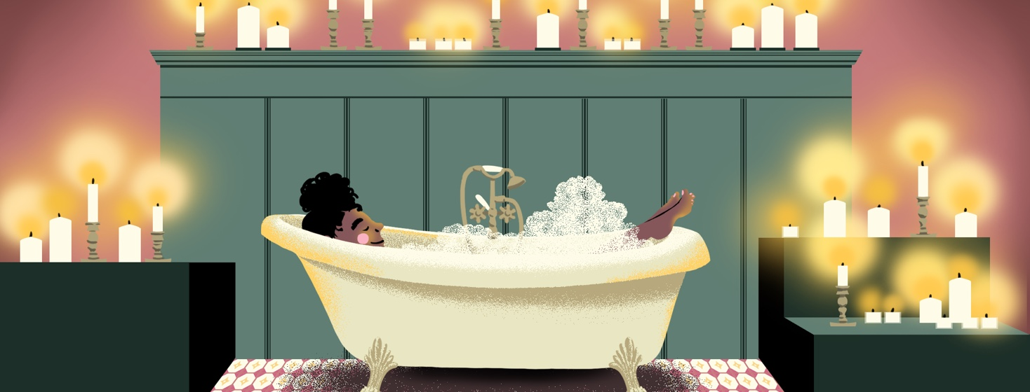A woman relaxes in her bath surrounded by candles
