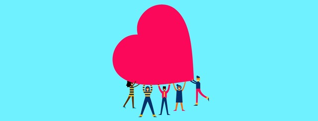 a group of people works together to hold a giant heart