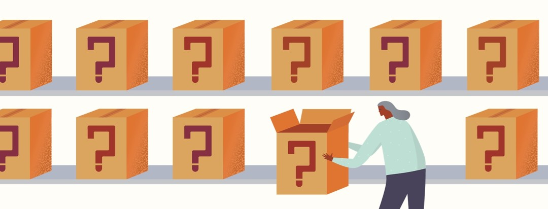 A woman is in front of shelving for boxes with question marks on them