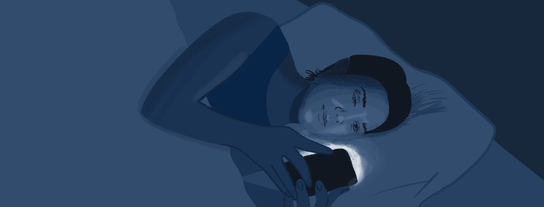 A woman looks at her phone in bed in the dark