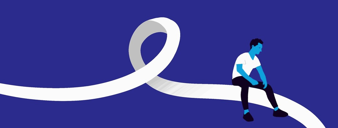 A person sits thoughtfully on a white cancer awareness ribbon