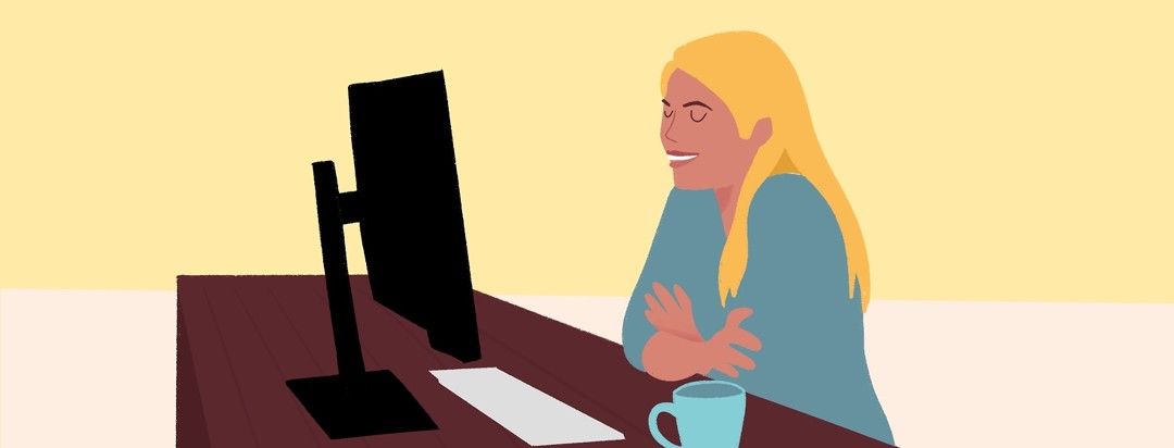 A woman smiles at her computer screen