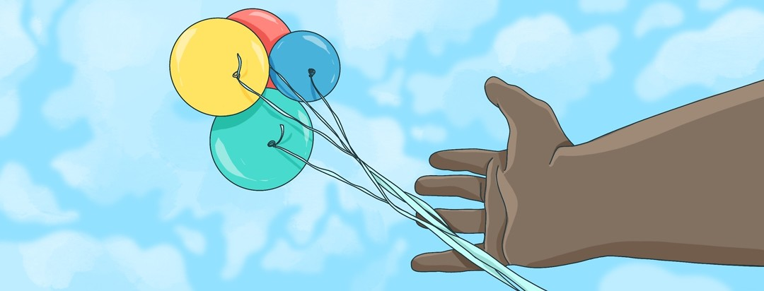 A hand releasing balloons in to the air