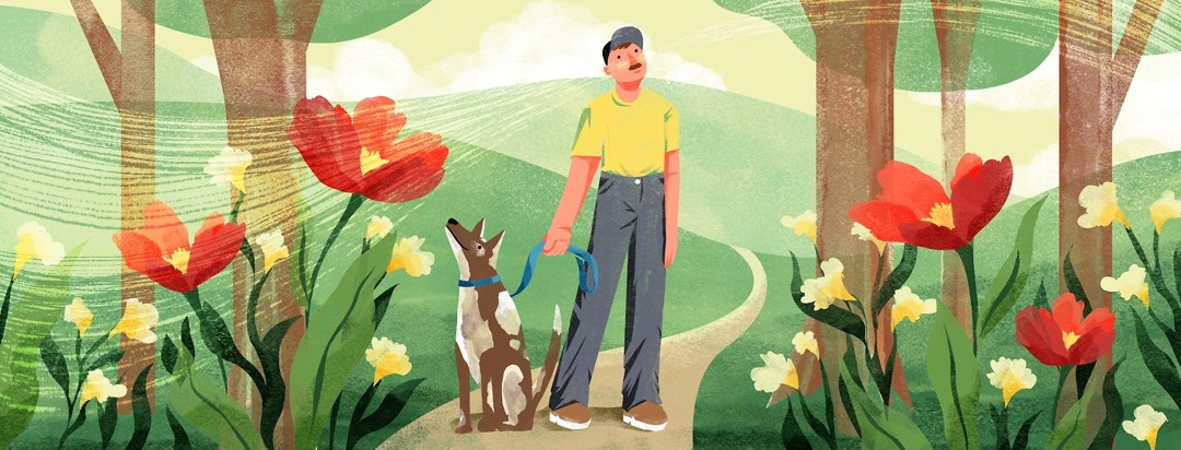 Man walking his dog takes a deep breath, smelling the flowers
