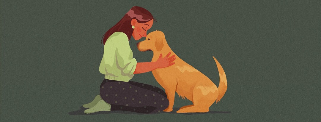 A woman and a dog snuggle
