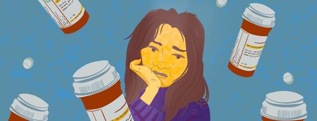 A woman looks sadly at bottles of prescription pills